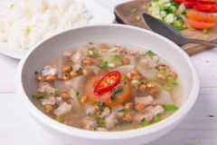 Soto or coto or indonesian beef soup served with white rice, tomato, soy, and green onion. On wood base Stock Photography