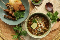 Soto Kudus. Chicken soup from Kudus city in Central Java, served complete with variety of accompaniments and green chili paste. The whole dish placed on royalty free stock photo