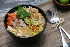 Soto Mie. Spicy beef noodle soup from Bogor, West Java. Plated in black ceramic bowl with spoon and fork on side. Arranged on plant-fiber mat Stock Images