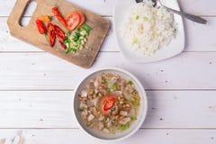 Soto o el coto o la sopa indonesia de la carne de vaca sirvieron con el arroz blanco, el tomate, la soja, y la cebolla verde Imagenes de archivo