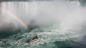 Sotto il cascate del Niagara con una barca e un arcobaleno di giro nello spruzzo stock footage