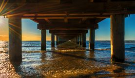Sotto il pilastro al bello tramonto arancio dorato fotografia stock