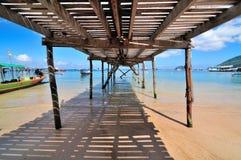 Sotto il ponte di legno ad una bella spiaggia Fotografia Stock