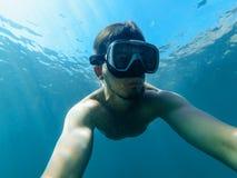 Sotto l'acqua l'uomo dell'operatore subacqueo nella maschera sta immergendosi Fotografia Stock Libera da Diritti