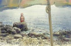 Sotto un ombrello di spiaggia Immagini Stock