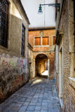 Sottopassaggio covered street, Venice, Italy. Sottopassaggio or small covered street in Venice, Venezia, Italy, Italia, with a street lattern and brick vintage royalty free stock photography