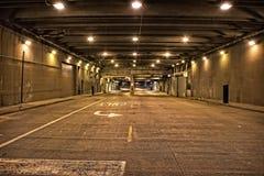 Sottopassaggio del centro scuro e granuloso del tunnel della via della città alla notte Immagine Stock