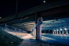 Sottopassaggio scuro granuloso della via del ponte stradale della città alla notte fotografia stock