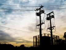 Sottostazione di elettricità della siluetta e alta tensione Palo Fotografie Stock