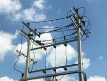Sottostazione elettrica ad alta tensione del palo contro cielo blu Fotografia Stock