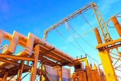 Sottostazione elettrica ad alta tensione per produzione e distribuzione della energia elettrica con illuminazione di notte Fotografia Stock Libera da Diritti