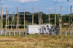Sottostazione elettrica che sta sull'erba fra gli alberi Immagine Stock