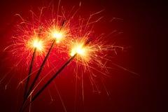 Sottragga gli sparklers su priorità bassa rossa Immagine Stock