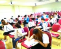 Sottragga gli studenti vaghi che fanno l'esame nella stanza di studio Fotografia Stock