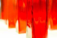 Sottragga la foto vaga delle bottiglie strutturate di vetro trasparente e di rosso i Immagini Stock