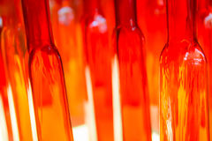 Sottragga la foto vaga delle bottiglie strutturate di vetro trasparente e di rosso i Fotografia Stock Libera da Diritti