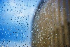sottragga la priorità bassa Gocce di acqua sulla finestra Grattacieli fotografia stock