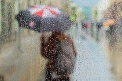 Sottragga la siluetta vaga della ragazza sotto l'ombrello, gocce di pioggia viste attraverso via della città sul vetro di finestr Immagine Stock Libera da Diritti