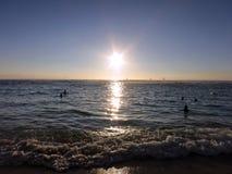 人们在水中观看在圣Souci海滩的剧烈的日落 免版税库存照片