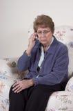 Souci parlant de téléphone portable aîné mûr de femme triste Images libres de droits