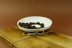Soucoupe avec des grains de café sur la planche à découper en bois avec un arc Images stock