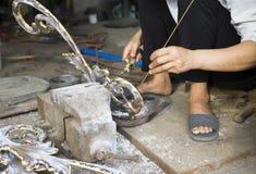 Soudeuse asiatique travaillant au côté de rue Photo stock