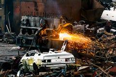 Soudeuse avec le fer à souder à l'intérieur d'un chantier de ferraille Image stock