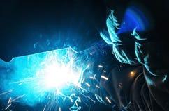 Soudeuse dans un masque protecteur dans des pièces en métal de soudage d'atelier d'obscurité Par la soudure les étincelles volent Photo libre de droits