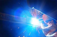 Soudeuse dans un masque protecteur dans des pièces en métal de soudage d'atelier d'obscurité Par la soudure les étincelles volent Image libre de droits