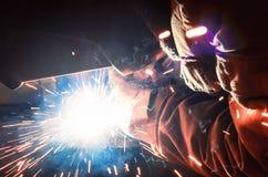 Soudeuse dans un masque protecteur dans des pièces en métal de soudage d'atelier d'obscurité Par la soudure les étincelles volent Photos stock