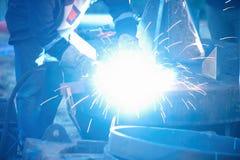 Soudeuse industrielle d'électrode avec le masque de protection et la soudure globale bleue un tuyau d'acier dans l'atelier Photo stock