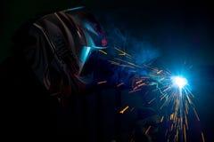 Soudeuse masculine dans un masque effectuant la soudure en métal Photo dans des couleurs fonc?es photos libres de droits