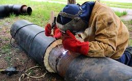 Soudeuse travaillant aux tubes en métal Photo libre de droits