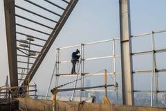 Soudure asiatique de travailleur sur le haut bâtiment sans échafaudage, basse condition de travail de sécurité photos stock