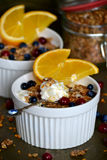 Soufflé with homemade granola and orange slices. In white plates on a metal tray Stock Photos