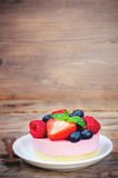 Souffle cake with fresh raspberries, blueberries and strawberrie. S on a dark wood background. toning. selective focus on mint Stock Images