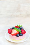 Souffle cake with fresh raspberries, blueberries and strawberrie. S on a white wood background. toning. selective focus on mint Stock Images