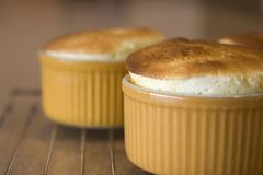 Souffles. Airy souffles cooling on a rack. Sharp focus on the left top edge of the front souffle Stock Image