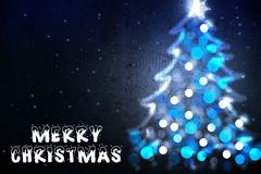 Souhait de Joyeux Noël sur la carte de voeux avec la silhouette d'arbre de Noël des lumières bleues Photographie stock libre de droits