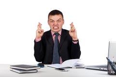 Souhaitant l'homme d'affaires croisant ses doigts dans son bureau d'isolement sur le fond blanc Photos stock