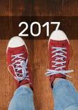 2017 souhaits de nouvelle année avec l'adolescent utilisant les espadrilles rouges Photos stock