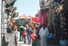 1974. Morocco. Souk in Marrakesh. A small group of tourist taking pictures and discovering the magic of the souks Stock Image