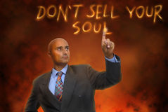 Soul. Businessman in hell writing in fire stock photo