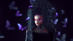 Soul breaks free from the cage. Young attractive girl in bright art-makeup, a lot of butterflies Stock Photos