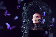 Soul breaks free from the cage. Young attractive girl in bright art-makeup, a lot of butterflies Stock Photo