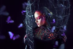 Soul breaks free from the cage. Young attractive girl in bright art-makeup, a lot of butterflies Stock Image