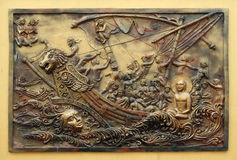 Soul itself is the strongest power; Sudamstra, a serpent-prince, creates a heavy storm in the river, but fails. Street bass relief on the wall of Jain Temple stock image