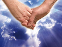 Soul and love. Two hands enhaced with a background of clouds and light of God. Concept of love, soul and friendship Stock Images