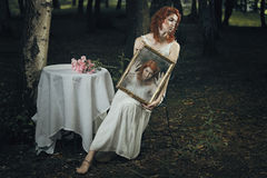 Soul of a woman trapped inside a mirror. In a strange forest . Dark and surreal Stock Photo
