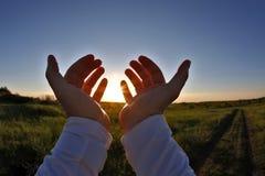 Soulevées mains à l'arrière-plan du coucher du soleil Photo libre de droits